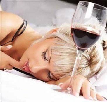 Уснувшая на столе девушка с бокалом вина