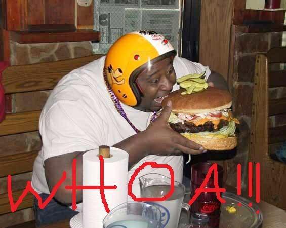 Толстый афроамериканец ест громадный гамбургер